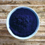blue spirulina extract natural color colour powder on wood background